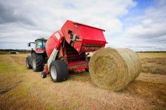 Traktor, der Heuschober auf dem Gebiet montiert Stockbilder