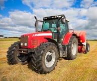 Traktor, der Heuschober auf dem Gebiet montiert Lizenzfreie Stockbilder