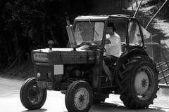 Traktor, der hinter die Straße fährt Lizenzfreies Stockfoto