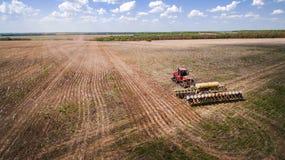 Traktor, der Land für das Säen von sechzehn Reihen von der Luft, von Konzept der Bearbeitung, Säen, Feld, Traktor und Produktion  stockfoto