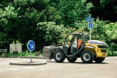 Traktor, der metallische Zaununterstützungen trägt Lizenzfreies Stockbild