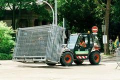 Traktor, der metallischen Zaun auf städtischer Straße trägt Stockbild