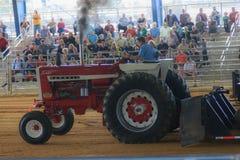 Traktor, der mit einem Weinlese Farmall-Traktor zieht Stockfotografie