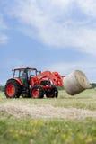 Traktor, der ringsum Ballen schleppt Stockfotografie