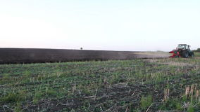 Traktor, der Schwarzerdepflugfeld bei Sonnenuntergang pflügt stock video