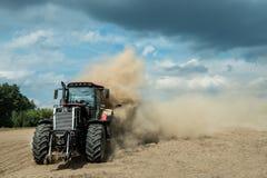 Traktor, der trockenes Ackerland am Herbst pflügt Lizenzfreie Stockfotografie