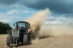 Traktor, der trockenes Ackerland am Herbst pflügt Lizenzfreie Stockfotos