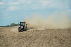 Traktor, der trockenes Ackerland am Herbst pflügt Stockbild