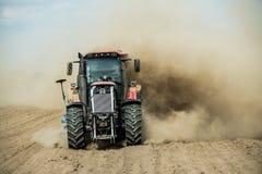 Traktor, der trockenes Ackerland am Herbst pflügt Lizenzfreies Stockbild