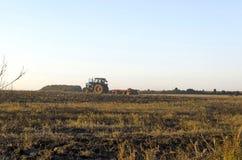 Traktor, der Weizenstoppelfeld mit Ernterückständen kultiviert Stockbild
