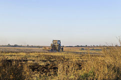 Traktor, der Weizenstoppelfeld mit Ernterückständen kultiviert Lizenzfreies Stockfoto