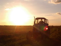 Traktor en puesta del sol Fotografía de archivo libre de regalías