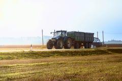 Traktor fährt auf die Asphaltstraße im Sonnenlicht Stockbilder