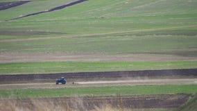 Traktor fährt durch das Feld in den Bergen stock video