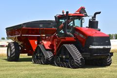 Traktor för nytt fall IH på spår och kornvagnen Royaltyfria Bilder