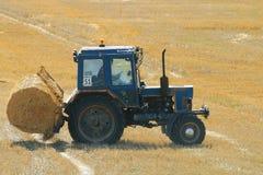 Traktor i ett fält av hö Arkivfoto