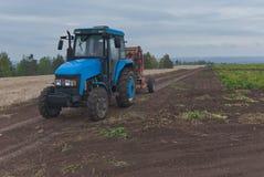 Traktor i ett potatisfält royaltyfri fotografi