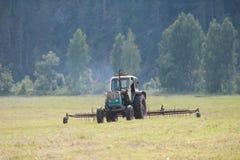 Traktor i hayfielden Royaltyfri Bild