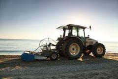 Traktor im Morgen nimmt Abfall weg auf Strand Lizenzfreies Stockbild