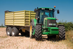 Traktor John Deere auf geerntetem Feld Stockfotografie