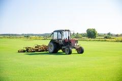 Traktor med en dysa för omsorg av en fältgräsmatta för en hästpolo i arbete Snitt-avgräset tar av från mekaniska delar av ett ing arkivfoto