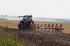 Traktor med plogen på åkermarkprocessar Arkivfoto
