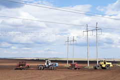 Traktor med seederen som sår arbeten Royaltyfria Bilder