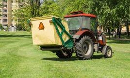 Traktor med släpet som mejar gräs Fotografering för Bildbyråer