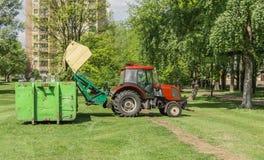 Traktor med släpet som mejar gräs Arkivbild