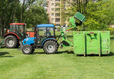 Traktor med släpet som mejar gräs Arkivfoton