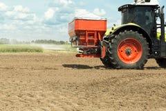 Traktor med sprejaresläpet bredvid det sädes- fältet Tungt maskineri för jordbruk arkivfoton