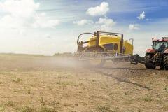 Traktor med sprejaresläpet bredvid det sädes- fältet Tungt maskineri för jordbruk royaltyfri foto