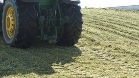 Traktor med videoen Hay Bales/4к från lantgårdar, var för bakgrundstraktor för blå himmel baksidan från fältet med ett hö _ Arkivbilder