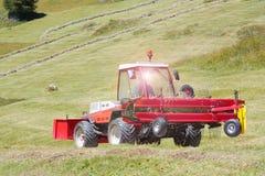 Traktor med windroweren & x28; swather& x29; rörande på en grusväg Royaltyfria Foton