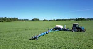 Traktor mit Anhängerbehälter spritzt Rapssamenfeld mit Chemikalien stock video footage
