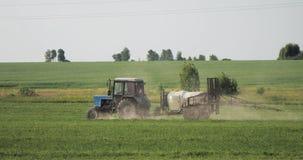 Traktor mit Düngemittel-Spreizer-Sprühschädlingsbekämpfungsmitteln oder Chemikalien auf Feld mit Sprüher am Frühling stock footage
