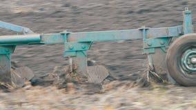 Traktor mit dem Pflug mit vier Furchen, der Feld mit schwarzem Bodenabschluß herauf Ansicht pflügt stock video