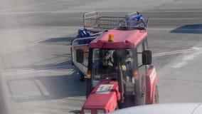 Traktor mit den leeren Gepäckwagen, die durch das Flugzeug überschreiten Personalauto bewegt sich nahe der Fläche stock video