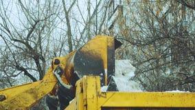 Traktor mit einem großen Eimer lädt Schnee stock video