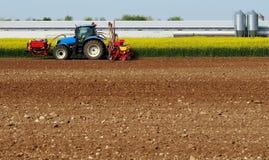 Traktor mit einer Säensamenmaschine und einer Düngemittelmaschine, wie Anhängern, auf einem gepflogenen Landfeld Stockbild