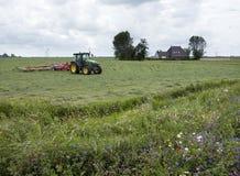 Traktor mit Gras Turner nahe Bauernhof in der niederländischen Provinz von Friesla Lizenzfreies Stockbild