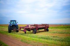 Traktor mit Mäher auf dem Gebiet der Esparsette und der Luzerne Lizenzfreie Stockbilder