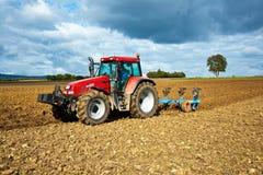 Traktor mit Pflug auf Feld Stockfotografie