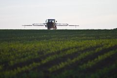Traktor mit Schädlingsbekämpfungsmittel auf Feld lizenzfreies stockbild