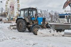 Traktor mit snowplowing Ausrüstung säubert Straße Lizenzfreie Stockfotos