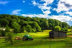 Traktor och ladugårdlantgårdlandskap arkivbild