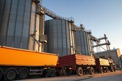 Traktor och lastbil bredvid kornsilor Arkivfoto