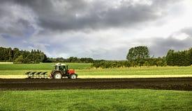 Traktor och plog i fält Royaltyfri Bild