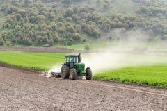 Traktor och plog i fält arkivbilder