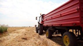 Traktor och sammanslutning på skördat fält Arkivbilder